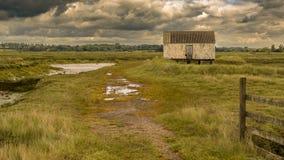 Marshland near the River Crouch, England, UK. House on stilts in the marshland near the River Crouch, Wallasea Island, Essex, England, UK Stock Photos