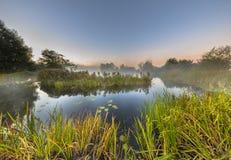Marshland river system under foggy morning sunrise Stock Photo