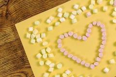 Marshmallow γλυκά που τοποθετούνται στη μορφή καρδιών έννοια ημέρας και αγάπης βαλεντίνων ` s σε κίτρινο χαρτί και το ξύλινο υπόβ Στοκ Φωτογραφίες