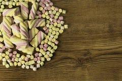 Marshmallow καραμέλες που τοποθετούνται στο κέντρο άλλων καραμελών Έννοια ημέρας και αγάπης βαλεντίνων ` s στο ξύλινο υπόβαθρο Στοκ Φωτογραφίες