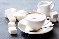 Marshmallow ραβδιά που βρίσκονται στο φλυτζάνι υποβάθρου με τη φρέσκια μαύρη κρέμα καφέ Στοκ Εικόνες