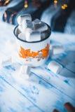 Marshmallow σε ένα φλυτζάνι σε ένα άσπρο υπόβαθρο με ένα μαντίλι Στοκ Εικόνες