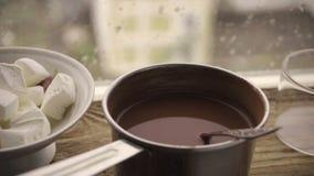 Marshmallow σε ένα φλυτζάνι, κακάο σε ένα τηγάνι saute σε μια στρωματοειδή φλέβα παραθύρων ενάντια στο παράθυρο φιλμ μικρού μήκους