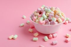 Marshmallow in bowl on pink background. Colorful marshmallow in white bowl on pink background Royalty Free Stock Images