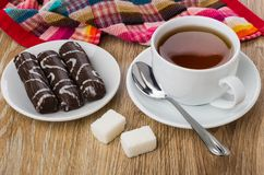 Marshmallow in chocolate in plate, cup of tea, sugar, teaspoon. On wooden table Royalty Free Stock Images