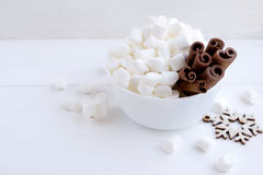 Marshmallow and cinnamon in bowl on white background Stock Photos