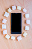 Marshmallow in circle around a black smart phone Royalty Free Stock Photos