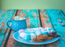 Marshmallow cookies and chocolate on blue plate Stock Images