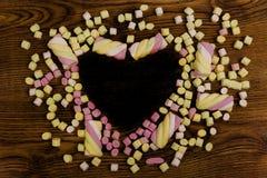Marshmallow cukierki z ciemnym kierowym kształtem Walentynki ` s dzień i miłości pojęcie na drewnianym tle zdjęcia royalty free