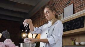 Marshmallow decoraiting do pasteleiro fêmea usando o açúcar pulverizado video estoque