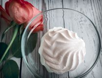 A marshmallow in a glass vase next to a rose. In a glass vase delicious marshmallow, next to a rose. The view from the top stock images