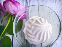 A marshmallow in a glass vase next to a rose. In a glass vase delicious marshmallow, next to a rose. The view from the top stock image
