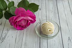 A marshmallow in a glass vase next to a rose. In a glass vase delicious marshmallow, next to a rose. The view from the top royalty free stock photo