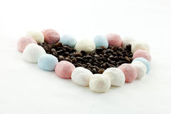 Marshmallow handicraft and coffee. Marshmallow forming a heart with coffee berries Royalty Free Stock Images