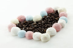 Marshmallow handicraft and coffee. Marshmallow forming a heart with coffee berries Royalty Free Stock Photo