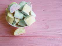 Marshmallow on a macro pink wooden yellow yummy lots sugar different. Marshmallow many on a pink wooden yellow sugar different yummy macro stock photos