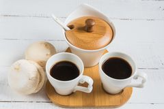 Marshmallow with marmalade, jug of milk, coffee in cup and sugar, spoon on wooden table stock images