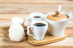 Marshmallow with marmalade, jug of milk, coffee in cup and sugar, spoon on wooden table royalty free stock photos