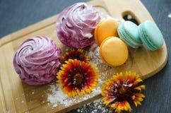 Marshmallow och makron med blommor och stänk arkivfoton