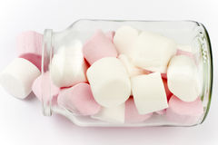Marshmallow sweets in a bottle. Soft pink and white marshmallow  candy spilling from a glass container Stock Photography