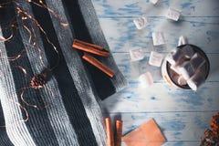 Marshmallow w filiżance na białym drewnianym tle z cynamonowymi kijami Obrazy Royalty Free
