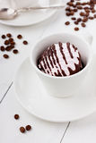 Marshmallow (zephyr) with coffee on a white cup. On a light wooden background Stock Image