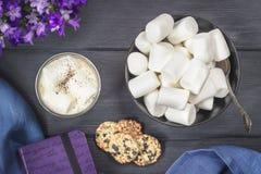 Marshmallower och varm kakao i en kopp med kakor och anteckningsboken Royaltyfri Foto