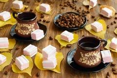 Marshmallows στα κίτρινα φύλλα και το φλιτζάνι του καφέ Στοκ Φωτογραφίες