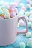 Marshmallows χρώματος κρητιδογραφιών σε ένα ρόδινο φλυτζάνι Στοκ Φωτογραφία
