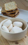 Marshmallows in bowl and smores. On wooden table Royalty Free Stock Images
