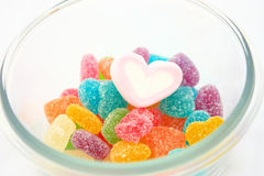 Marshmallows and candy in a bowl isolated. Heart shape marshmallow around by colorful candy in a bowl isolated on white stock image