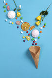 Marshmallows, candy, jelly beans, sweets and dry mugs oranges falling in wafer cone on blue background. Marshmallows, candy, jelly beans, sweets , dry mugs Royalty Free Stock Image