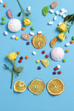 Marshmallows, candy, jelly beans, sweets and dry mugs oranges falling in wafer cone on blue background. Marshmallows, candy, jelly beans, sweets , dry mugs Stock Image