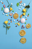 Marshmallows, candy, jelly beans, sweets and dry mugs oranges falling in wafer cone on blue background. The Marshmallows, candy, jelly beans, sweets , dry mugs Royalty Free Stock Photography