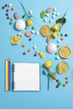 Marshmallows, candy, jelly beans, sweets , dry mugs oranges and yellow roses falling on a notepad on a blue background. Advertisin. G Space Stock Photography