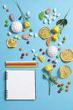 Marshmallows, candy, jelly beans, sweets , dry mugs oranges and yellow roses falling on a notepad on a blue background. Advertisin. G Space Royalty Free Stock Photography
