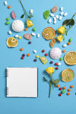 Marshmallows, candy, jelly beans, sweets , dry mugs oranges and yellow roses falling on a notepad on a blue background. Advertisin. The Marshmallows, candy Royalty Free Stock Photos
