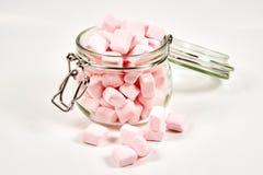 Marshmallows cor-de-rosa no frasco de vidro, no fundo branco imagem de stock royalty free
