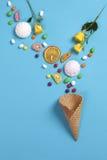 Marshmallows, cukierek, galaretowe fasole, cukierki i suszą kubek pomarańcze spada w opłatka rożku na błękitnym tle obraz royalty free