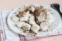 Marshmallows dusted with cocoa on white plate Stock Photo