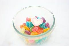 Marshmallows e doces em uma bacia isolada Foto de Stock