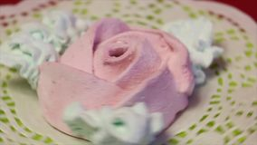 Marshmallows in the form of a rose. With petals. Lies on a lacy napkin. Rotates around a vertical axis stock video