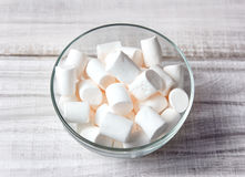 Marshmallows in glass bowl closeup on wooden background. Royalty Free Stock Image