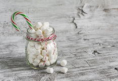 Marshmallows in a glass jar and candy - Christmas gift,  on a light wooden surface Stock Image