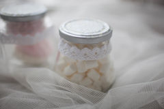 Marshmallows in a glass jar on a white cloth. Closeup royalty free stock images
