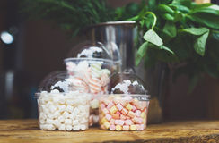 Marshmallows in glass jars on bar for sale. Desserts choice. Marshmallow chewing candies in glass jars on counter bar for sale. Traditional american sweets for Stock Photography