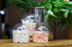 Marshmallows in glass jars on bar for sale. Desserts choice. Marshmallow chewing candies for hot chocolate topping in glass jars on counter bar for sale Royalty Free Stock Photography