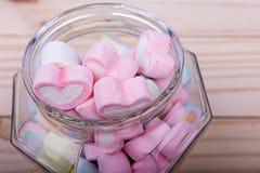Marshmallows in jar on wooden table Stock Photos