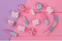 Marshmallows and jellies on color background. stock image