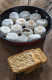 Marshmallows and pile of crackers. On wooden table Royalty Free Stock Photo